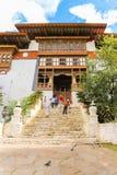 Paro Bhutan - September 10, 2016: Sikt för låg vinkel av turister som står på trappa för en gammal tempel Arkivfoto
