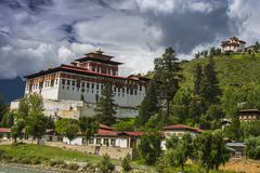 Paro Dzong e tum Dzong con le nuvole di galleggiamento, Paro, Bhutan immagine stock