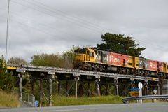 Rail bridge. PAROA, NEW ZEALAND, NOVEMBER 18, 2017: A freight train crosses an old wooden bridge near Paroa, New Zealand Royalty Free Stock Image