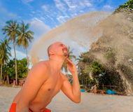 Parody of girls: sand on the bald head is like flying hair.  Stock Photos