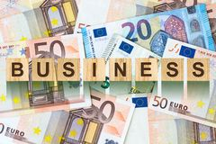 Parola, affare composto di lettere sulle particelle elementari di legno contro lo sfondo di euro banconote Affare di concetto, fi Fotografie Stock