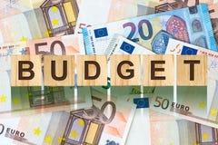 Parola, bilancio composto di lettere sulle particelle elementari di legno contro lo sfondo di euro banconote Affare di concetto,  Fotografia Stock