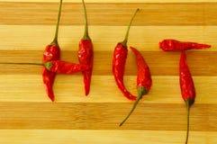 Parola CALDA fatta dai peperoncini rossi sul bordo di legno Fotografia Stock Libera da Diritti