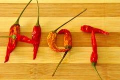 Parola CALDA fatta dai peperoncini rossi sul bordo di legno Fotografia Stock
