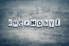 Parola Cernobyl dalle lettere tagliate su fondo grigio Concetto ecologico di catastrofe Titolo - Cernobyl Una parola che scrive t immagini stock