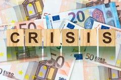 Parola, crisi composta di lettere sulle particelle elementari di legno contro lo sfondo di euro banconote Affare di concetto, fin Immagini Stock
