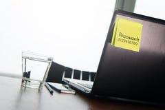 Parola d'ordine facile sulla nota appiccicosa sul computer portatile posteriore Fotografie Stock