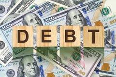 Parola, debito composto di lettere sulle particelle elementari di legno contro lo sfondo delle banconote in dollari Affare di con Immagine Stock