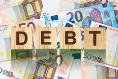Parola, debito composto di lettere sulle particelle elementari di legno contro lo sfondo di euro banconote Affare di concetto, fi Fotografia Stock Libera da Diritti