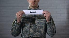 Parola dei braccia scritta sul segno in mani del soldato maschio, arsenale dell'arma, industria video d archivio