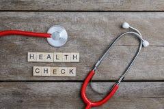 Parola del testo del controllo sanitario fatta con i blocchi di legno ed il cuore rosso, steth Immagini Stock