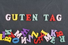 Parola dell'ETICHETTA di GUTEN sul fondo nero composto dalle lettere di legno di ABC del blocchetto variopinto di alfabeto, spazi fotografia stock libera da diritti