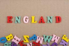 Parola dell'INGHILTERRA su fondo di carta composto dalle lettere di legno di ABC del blocchetto variopinto di alfabeto, spazio de Fotografie Stock
