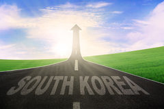 Parola della Corea del Sud con la freccia verso l'alto sulla strada Fotografia Stock