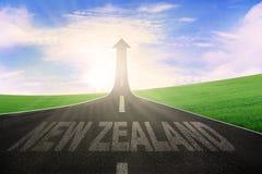 Parola della Nuova Zelanda con la freccia verso l'alto sulla strada Fotografia Stock Libera da Diritti