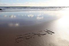 Parola della spiaggia scritta in sabbia Fotografie Stock