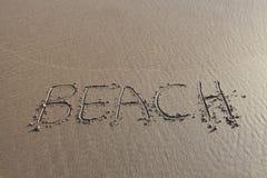Parola della spiaggia scritta in sabbia Immagine Stock