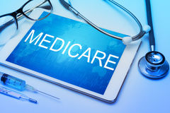 Parola di Assistenza sanitaria statale sullo schermo della compressa con attrezzatura medica fotografia stock