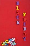 Parola di BLACK FRIDAY su fondo rosso composto dalle lettere di legno di ABC del blocchetto variopinto di alfabeto, spazio della  Fotografia Stock