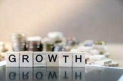 Parola di crescita scritta nella riflessione di legno del cubo sui wi neri dello specchio fotografia stock