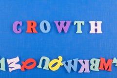Parola di crescita su fondo blu composto dalle lettere di legno di ABC del blocchetto variopinto di alfabeto, spazio della copia  fotografia stock libera da diritti
