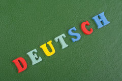 Parola di DEUTSCH su fondo verde composto dalle lettere di legno di ABC del blocchetto variopinto di alfabeto, spazio della copia Immagini Stock Libere da Diritti