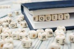 Parola di EQUITÀ scritta sul blocco di legno ABC di legno Fotografia Stock