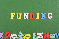 Parola di FINANZIAMENTO su fondo verde composto dalle lettere di legno di ABC del blocchetto variopinto di alfabeto, spazio della Fotografia Stock Libera da Diritti