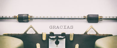 Parola di GRACIAS in lettere maiuscole su uno strato della macchina da scrivere Immagini Stock