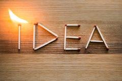 Parola di IDEA dalle partite con la fiamma su fondo di legno Immagine Stock
