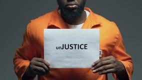 Parola di ingiustizia su cartone in mani del prigioniero afroamericano, disordine archivi video