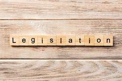 Parola di legislazione scritta sul blocco di legno testo sulla tavola, concetto di legislazione immagini stock