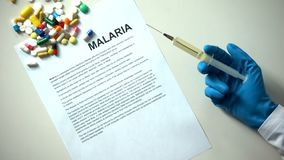 Parola di malaria scritta su carta, sulla mano di medico con le pillole della siringa e sulle compresse sulla tavola immagini stock