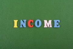 Parola di REDDITO su fondo verde composto dalle lettere di legno di ABC del blocchetto variopinto di alfabeto, spazio della copia Immagine Stock Libera da Diritti