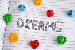 Parola di sogni sullo strato del taccuino con alcune palle di carta sgualcite variopinte su  fotografia stock libera da diritti