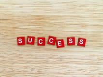 Parola di successo, alfabeto inglese bianco sui piatti rossi del magnete sul pavimento di legno della tavola Fotografia Stock