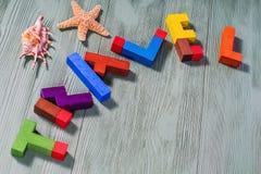 Parola di viaggio dei puzzle di legno variopinti con le coperture e le stelle marine Fotografie Stock