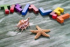 Parola di viaggio dei puzzle di legno variopinti con le coperture e le stelle marine Fotografie Stock Libere da Diritti