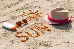 Parola e forma del sole, degli occhiali da sole, della lozione del sole e del cappello di paglia sulla sabbia alla spiaggia, conc Immagine Stock