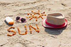 Parola e forma del sole, degli occhiali da sole, della lozione del sole e del cappello di paglia sulla sabbia alla spiaggia, ora  Fotografia Stock Libera da Diritti