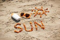 Parola e forma del sole, occhiali da sole con la lozione del sole sulla sabbia alla spiaggia, ora legale Fotografie Stock Libere da Diritti