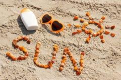 Parola e forma del sole, occhiali da sole con la lozione del sole sulla sabbia alla spiaggia, ora legale Fotografia Stock Libera da Diritti