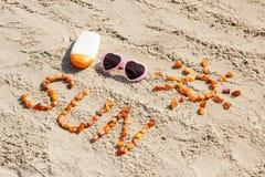 Parola e forma del sole, occhiali da sole con la lozione del sole sulla sabbia alla spiaggia, ora legale Immagine Stock Libera da Diritti