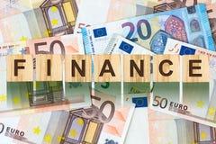 Parola, finanza composta di lettere sulle particelle elementari di legno contro lo sfondo di euro banconote Affare di concetto, f Immagine Stock