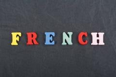 Parola FRANCESE sul fondo nero composto dalle lettere di legno di ABC del blocchetto variopinto di alfabeto, spazio del bordo del Immagine Stock Libera da Diritti