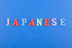 Parola GIAPPONESE su fondo blu composto dalle lettere di legno di ABC del blocchetto variopinto di alfabeto, spazio della copia p Immagini Stock
