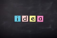 Parola & x27; Idea& x27; scritto sugli autoadesivi di colore sulla lavagna Fotografie Stock
