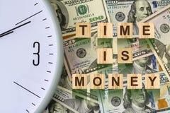 Parola, Il tempo è denaro composta di lettere sulle particelle elementari di legno contro lo sfondo delle banconote in dollari Af Immagini Stock