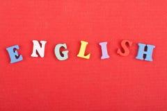 Parola inglese su fondo rosso composto dalle lettere di legno di ABC del blocchetto variopinto di alfabeto, spazio della copia pe immagine stock