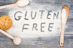 Parola libera del glutine scritta su farina e sulla tavola di legno Immagini Stock Libere da Diritti